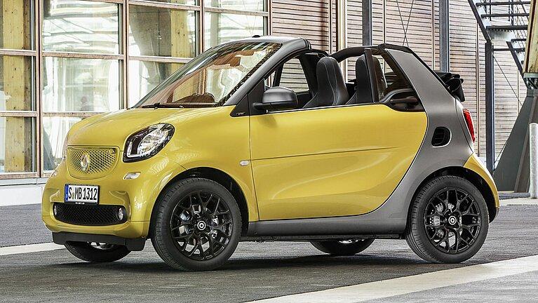 Seitliche Frontansicht des smart fortwo cabrio in gelb mit offenem Verdeck